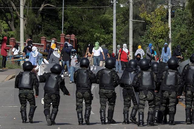 REPRESIÓN. Estudiantes universitarios con sus rostros cubiertos se enfrentan policías militares del Orden Público en Tegucigalpa.
