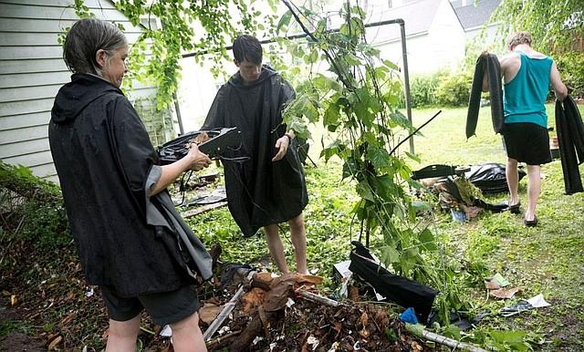 Bonnie Burns, a la izquierda, tiene un tocadiscos mientras ella, Micah Arye y Stephen Ray reúnen artículos que fueron arrastrados desde el sótano de su casa en Waverly Hills, en Arlington. | Foto: Marlena Sloss/El Washington Post.