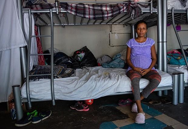 """En el refugio, Jiménez Martínez comparte el nivel inferior de una litera con su esposo. """"Es difícil dormir porque los bebés se mueven mucho y me mantienen despierta toda la noche"""", dijo. La comida no está garantizada en el refugio, por lo que su esposo corta el pelo para comprar un poco más de comida. """"Tengo antojos, pero no tenemos dinero para una nutrición adecuada"""", contó. (Heidi de Marco/KHN)"""