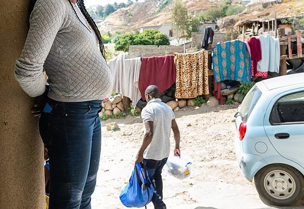 Daniela Pierre espera mientras su marido lleva la ropa para lavar. Pierre huyó de Haití hace cuatro años después que la economía colapsara y terminara en Venezuela. Pero dijo que la agitación política allí la obligó a seguir moviéndose, y pasó cuatro meses viajando en autobús y caminando hacia la frontera de los Estados Unidos. Ha estado viviendo en el refugio de Tijuana durante tres meses, mientras que el gobierno de los Estados Unidos considera su solicitud de asilo. (Heidi de Marco/KHN)