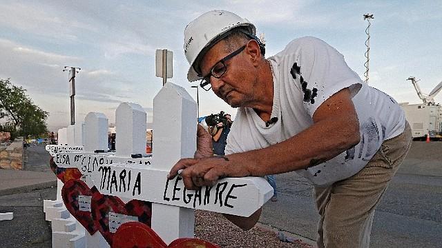 HOMENAJE. Un hombre coloca varias cruces en homenaje a las 20 víctimas mortales asesinadas el pasado sábado en un supermercado Walmart de El Paso, Texas