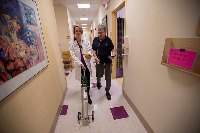 La doctora Mary Rice acompaña a Michael Howard en la Beth Israel Deaconess HealthCare Clinic en Chelsea, Massachussetts, mientras Howard prueba los niveles de oxígeno agregados en su tanque de oxígeno portátil. Howard tiene enfermedad pulmonar obstructiva crónica (EPOC), una condición progresiva de los pulmones que puede agravarse con el calor y la humedad. (Jesse Costa/WBUR)
