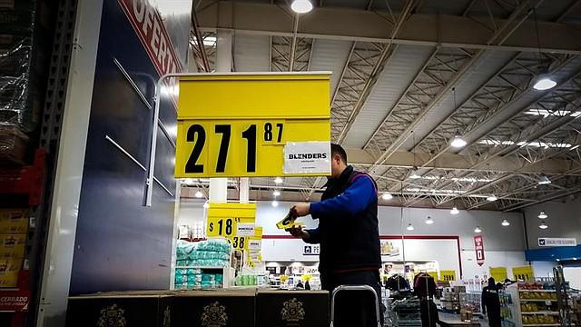 ARGENTINA. Un empleado cambia este miércoles los precios de los productos a causa de la inflación en un supermercado, en Buenos Aires