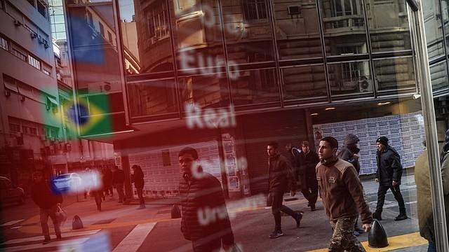 ECONOMÍA. Transeúntes caminan frente a una pantalla con la cotización del peso sobre monedas extranjeras este martes en Buenos Aires. | Foto: EFE/Juan Ignacio Roncoroni