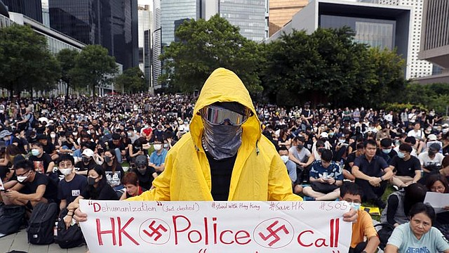 """MUNDO. Un manifestante prodemocrático sostiene una pancarta ilustrada con esvásticas en la que se lee """"la policía de Hong Kong califica a los manifestantes de cucarachas"""""""