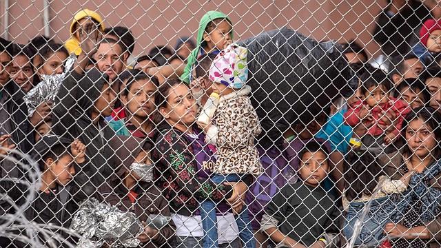 DETENIDOS. Migrantes detrás de la cerca de un improvisado centro de detención estadounidense en El Paso en marzo. | Foto: Sergio Flores para The Washington Post