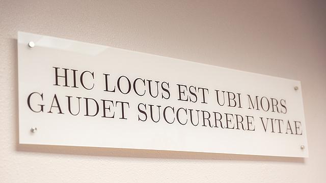 En la pared de la oficina de la epidemióloga del condado de Washington, Kimberly Repp, hay un letrero en latín: Hic locus est ubi mors gaudet succurrere vitae. Este es un lugar en donde los muertos se deleitan en ayudar a los vivos (Adam Wickham para KHN).