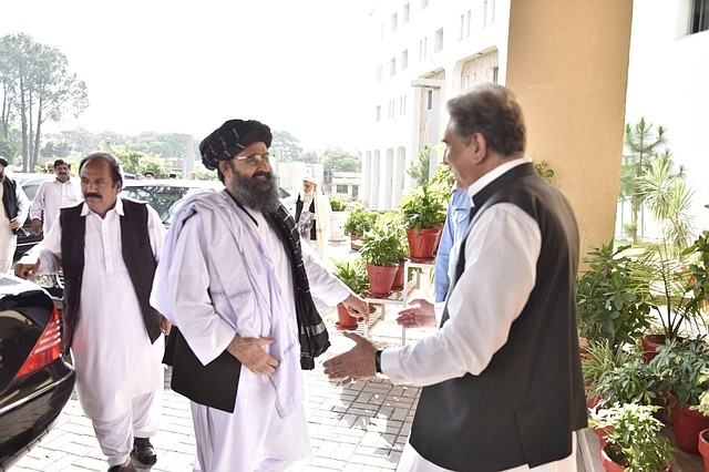 El ministro de Relaciones Exteriores de Pakistán, Shah Mehmood Qureshi (derecha), mientras saluda al cofundador y líder político del movimiento talibán Mullah Abdul Ghani Baradar (2-derecha) durante su reunión en Islamabad, el jueves 3 de Octubre de 2019.   Foto: Efe.