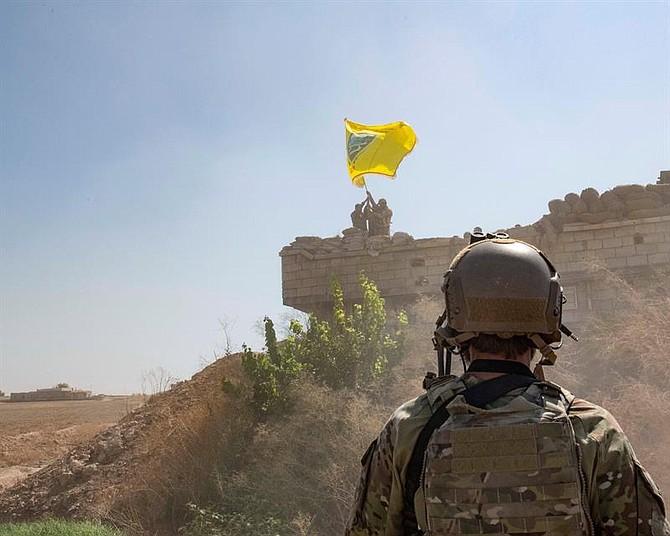 CONFLICTO. Imagen de archivo que muestra a un soldado estadounidense mientras supervisa a miembros de las Fuerzas Democráticas Sirias cuando derriban una fortificación de YPG (Unidades de Protección Popular, una milicia principalmente kurda en Siria) y levantan una bandera del Consejo Militar Tal Abyad sobre el puesto avanzado como parte del acuerdo de zona del mecanismo de seguridad, Siria,  el 21 de septiembre de 2019. Foto: Efe.