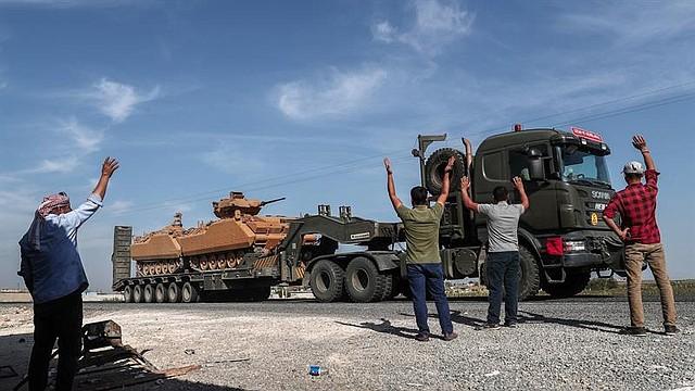 MUNDO. La gente se alegra mientras los vehículos militares turcos que transportan tanques se dirigen al norte de Siria para una operación militar en las zonas kurdas, cerca de la frontera con Siria, cerca del distrito de Akcakale en Sanliurfa, Turquía 14 de octubre de 2019