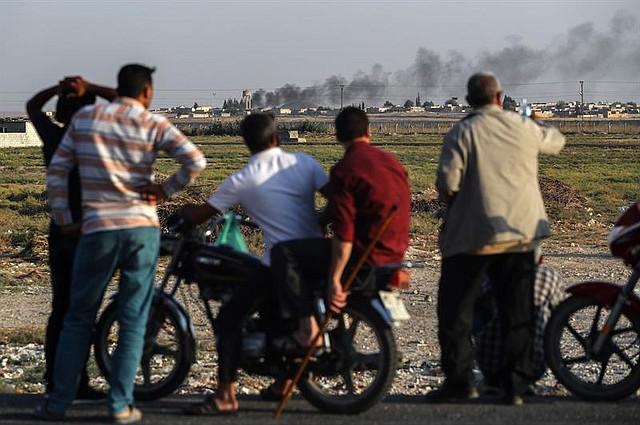 CONFLICTO. Varias personas observan la frontera turco-siria mientras el humo se eleva desde objetivos dentro de Siria. Vista desde el distrito de Akcakale en Sanliurfa, Turquía, el 13 de octubre de 2019. | Foto: Efe.