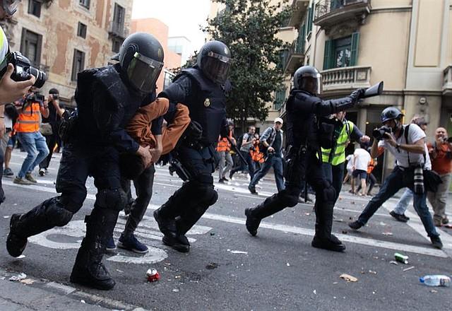Momento en el que agentes de la Policía Nacional detienen a un joven durante disturbios registrados en la Via Laietana, en Barcelona, el viernes 18 de octubre.   Foto: Efe/Enric Fontcuberta