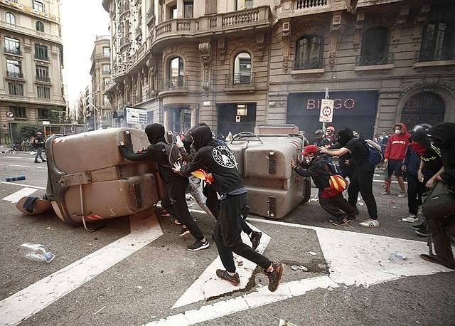 PROTESTAS. Manifestantes atravesaron obstáculos en la Via Laietana mientras se enfrentaban a los policías.   Foto: Efe/Jesús Diges