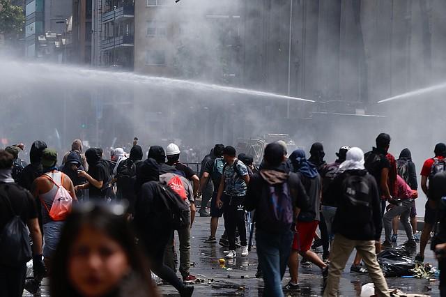 DISTURBIOS. Funcionarios de seguridad de Chile reprimen las manifestaciones con bombas lacrimógenas y vehículos antimotines.   Foto: Efe/Alberto Valdes.