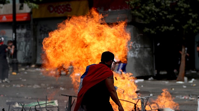 DESTROZOS. Un manifestante frente a una barricada en llamas durante el sexto día de protestas en el centro de Santiago, el miércoles 23 de octubre. | Foto: Efe/Fernando Bizerra Jr.