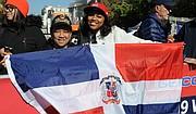 ALEGRES. La salvadoreña Mirna Ochoa (izq.) y la dominicana Giselle Rodríguez con la bandera de la República Dominicana / José Luis Argueta