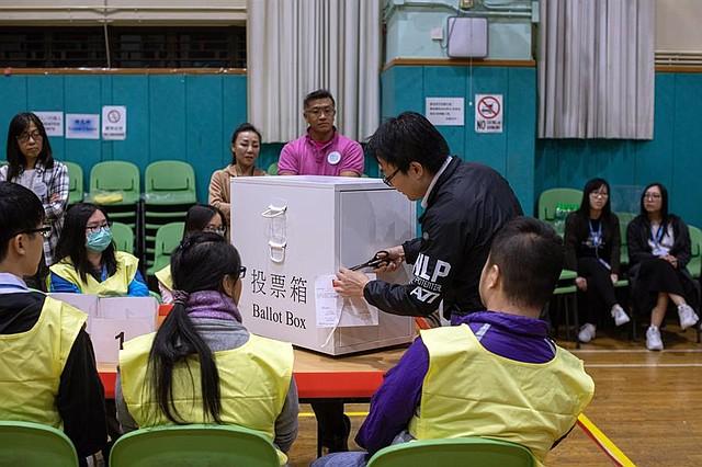 VOTACIONES. Personal de la Oficina de Registro y Electoral se prepara para abrir una urna durante las Elecciones Ordinarias del Consejo de Distrito en Hong Kong, China, el 24 de noviembre de 2019