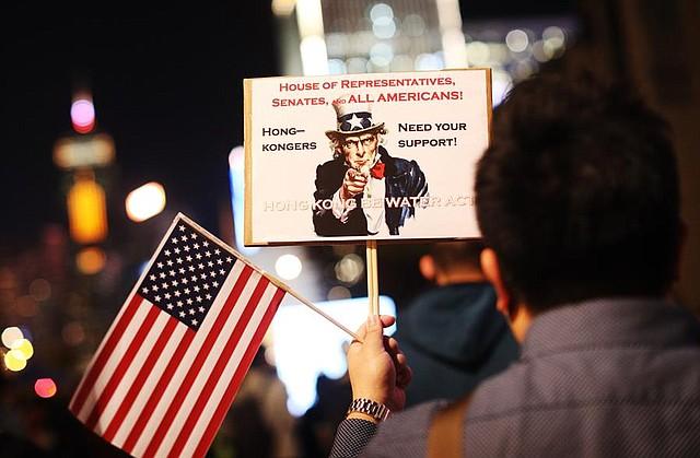 MUNDO. Un manifestante a favor de la democracia sostiene una pancarta y una bandera nacional de Estados Unidos durante una manifestación del Día de Acción de Gracias en Edimburgo Place, Hong Kong, China, el 28 de noviembre de 2019
