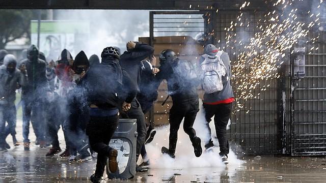 PROTESTA. Manifestantes se enfrentan con agentes del Escuadrón Móvil Anti-Disturbios tras una protesta contra el gobierno del presidente Iván Duque, en Bogotá el martes 10 de diciembre. | Efe/ Mauricio Dueñas Castañeda.