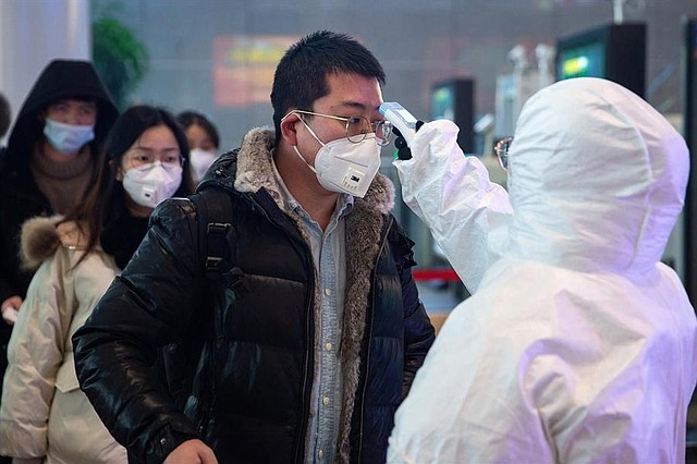SALUD. Personal médico verifica la temperatura de los pasajeros en la estación de ferrocarril del sur de Nanjing, en la provincia de Jiangsu, China, el 27 de enero. | Foto: Efe.