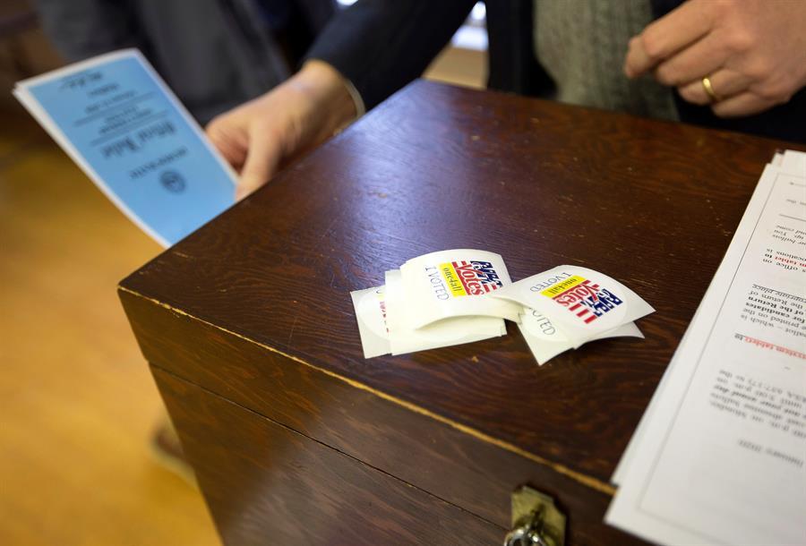 ELECCIONES. Se coloca una papeleta oficial en la urna de madera después de que el votante haya depositado su voto el día de las elecciones en el Ayuntamiento de Madbury, en Madbury, New Hampshire (EE.UU.), el 11 de febrero de 2020
