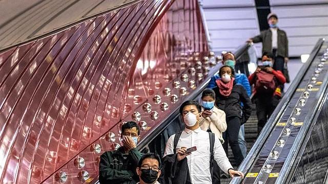 SALUD. La gente sube a la escalera mecánica de la estación de ferrocarril principal de Guangzhou con máscaras protectoras para proteger el Covid-19 en Guangzhou, China, el 12 de febrero de 2020