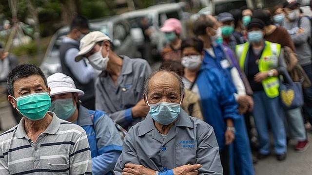 SALUD. Limpiadores de calles hacen cola para recibir máscaras faciales gratis en Hong Kong, China, 14 de febrero de 2020