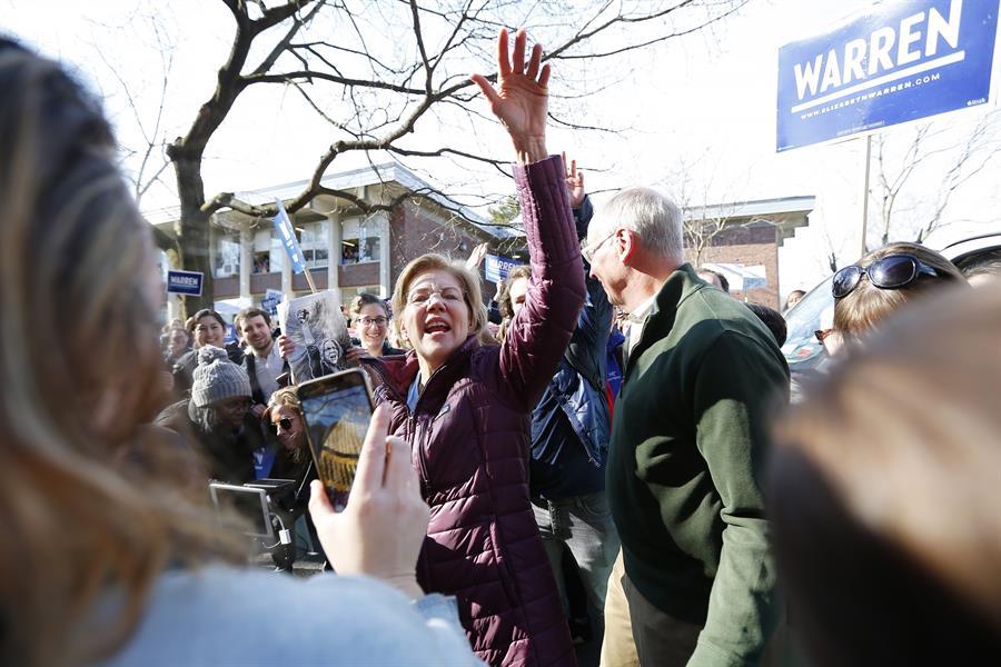 ELECCIONES. La senadora y candidata presidencial demócrata de Massachusetts Elizabeth Warren (C) y su esposo Bruce Mann (R) saludan a sus seguidores mientras caminan hacia un centro de votación para votar el Súper Martes en Cambridge, Massachusetts, EE.UU., 03 de marzo de 2020