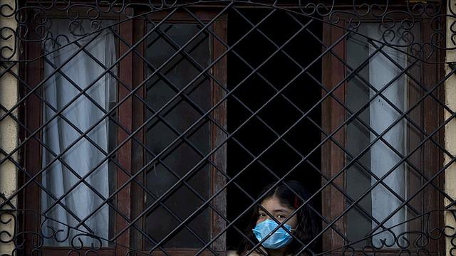 PREVENCIÓN. Una joven se asoma por una ventana con un tapabocas en Managua, Nicaragua. Foto: Efe/Jorge Torres.