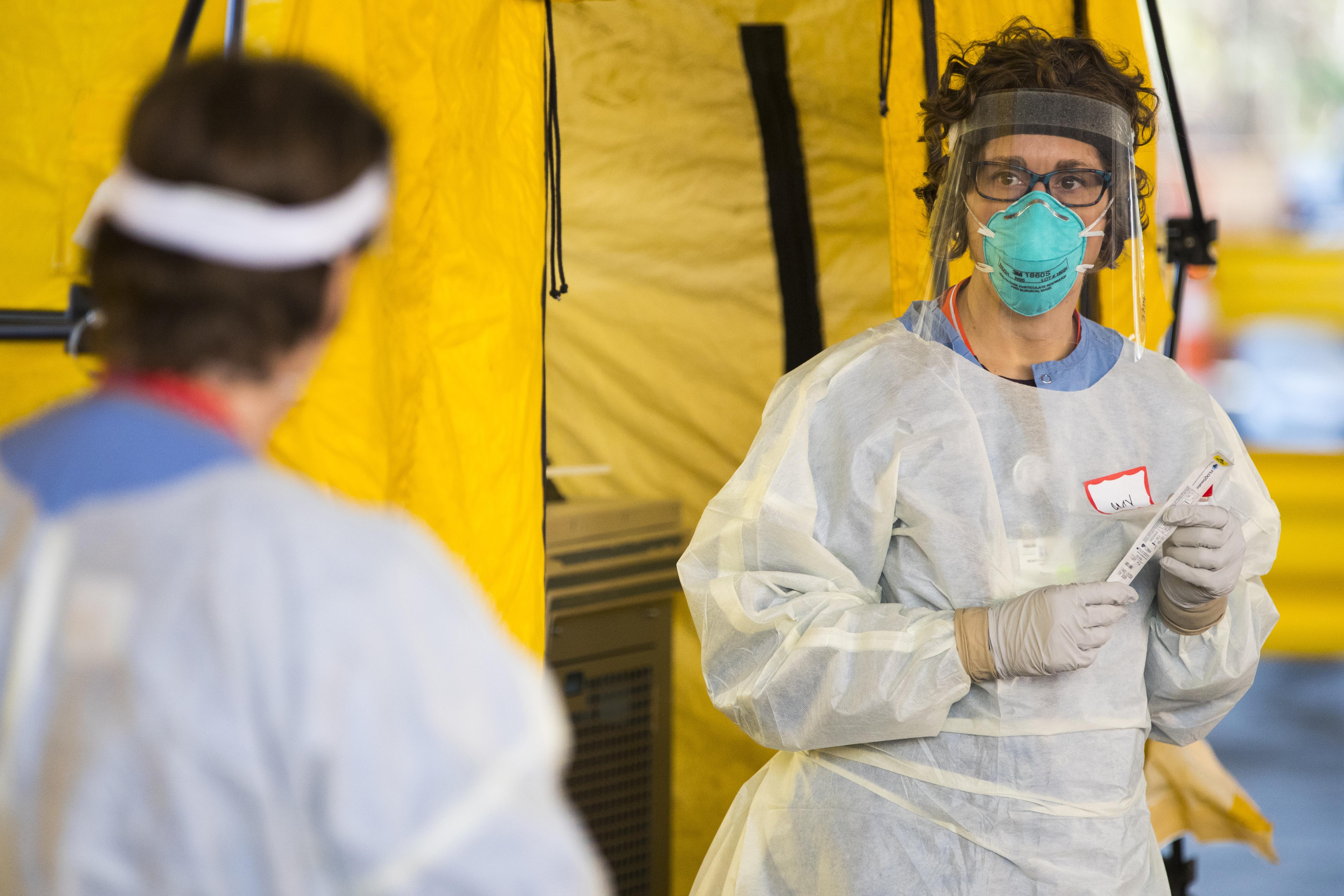 CRISIS. Una enfermera sostiene un test de coronavirus en el estacionamiento del Newton-Wellesley Hospital en Newton, Mass. | Photo for The Washington Post by Adam Glanzman.