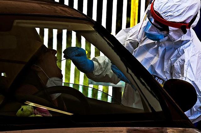 MUNDO. Un trabajador sanitario que lleva un mono y una máscara protectora realiza una prueba de hisopado a un automovilista sentado en su coche en Pozzuoli, cerca de Nápoles, Italia, 16 de abril de 2020
