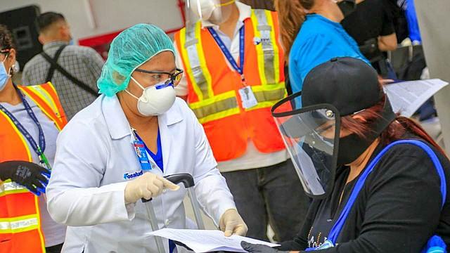 PREVENCIÓN. Una mujer supervisa los papeles de una viajera salvadoreña que regresó el martes procedente de Colombia, luego de quedar varada por dos meses debido al cierre del aeropuerto de El Salvador. | Foto: Efe.