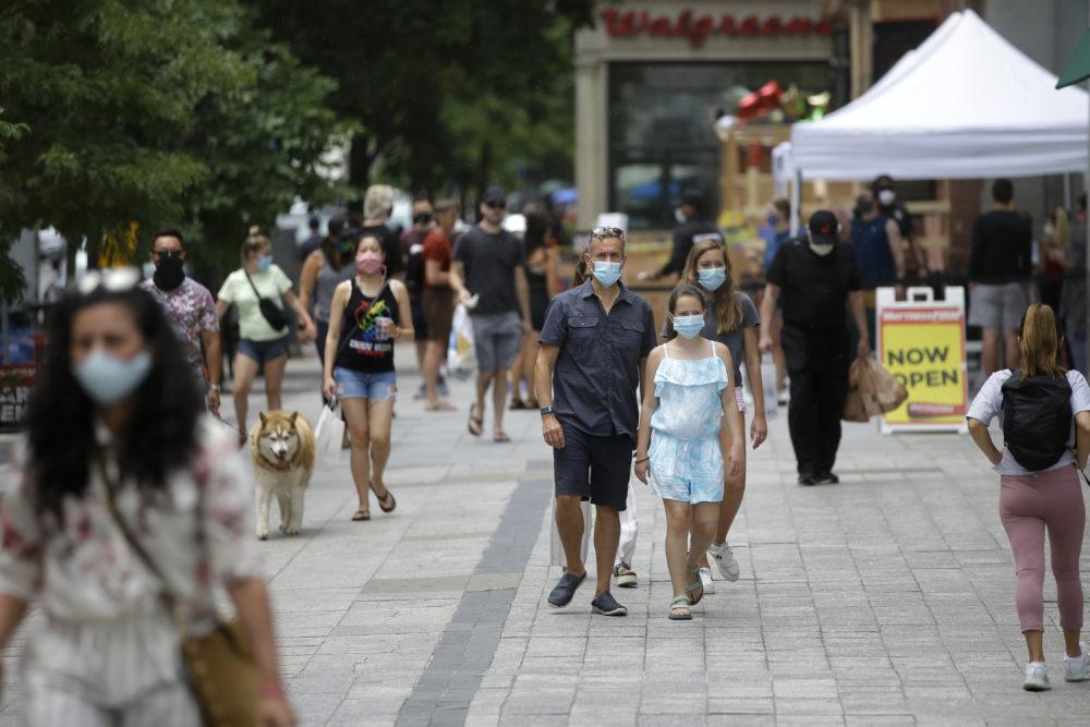 Peatones usan máscaras por preocupación por el coronavirus mientras caminan por una acera, en Boston el 28 de junio de 2020 (Steven Senne / AP)