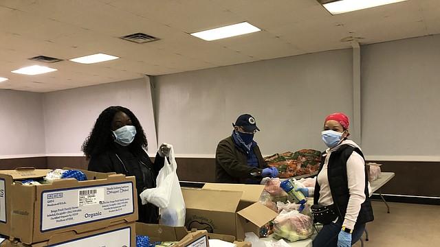 Alimentos. Personal de SEED y de Kaiser Permanente (centro) preparan las fundas de alimentos a ser entregados a la comunidad de Greater Riverdale.    FOTO: Cortesía SEED