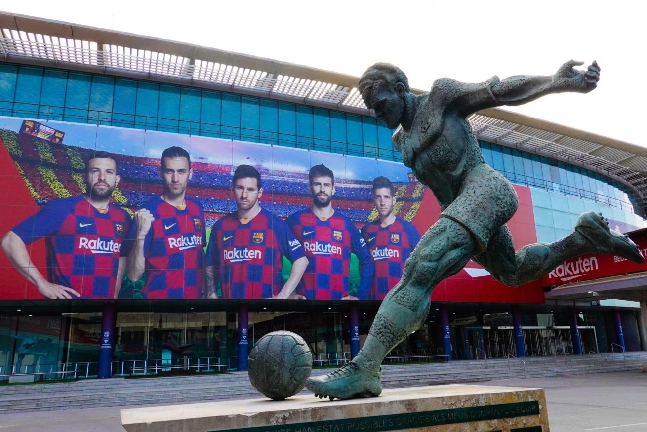 DEPORTE. Vista de la estatua dedicada a Kubala con un cartel publicitario en el Camp Nou , días después de que Messi pidió la carta de libertad del Barcelona. | Foto: Efe/Alejandro García.