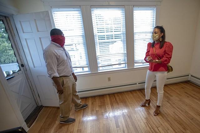 El agente inmobiliario Jonathan Viciere y la propietaria del condominio Mindy Wright esperan a que los posibles inquilinos se presenten en la jornada de puertas abiertas.