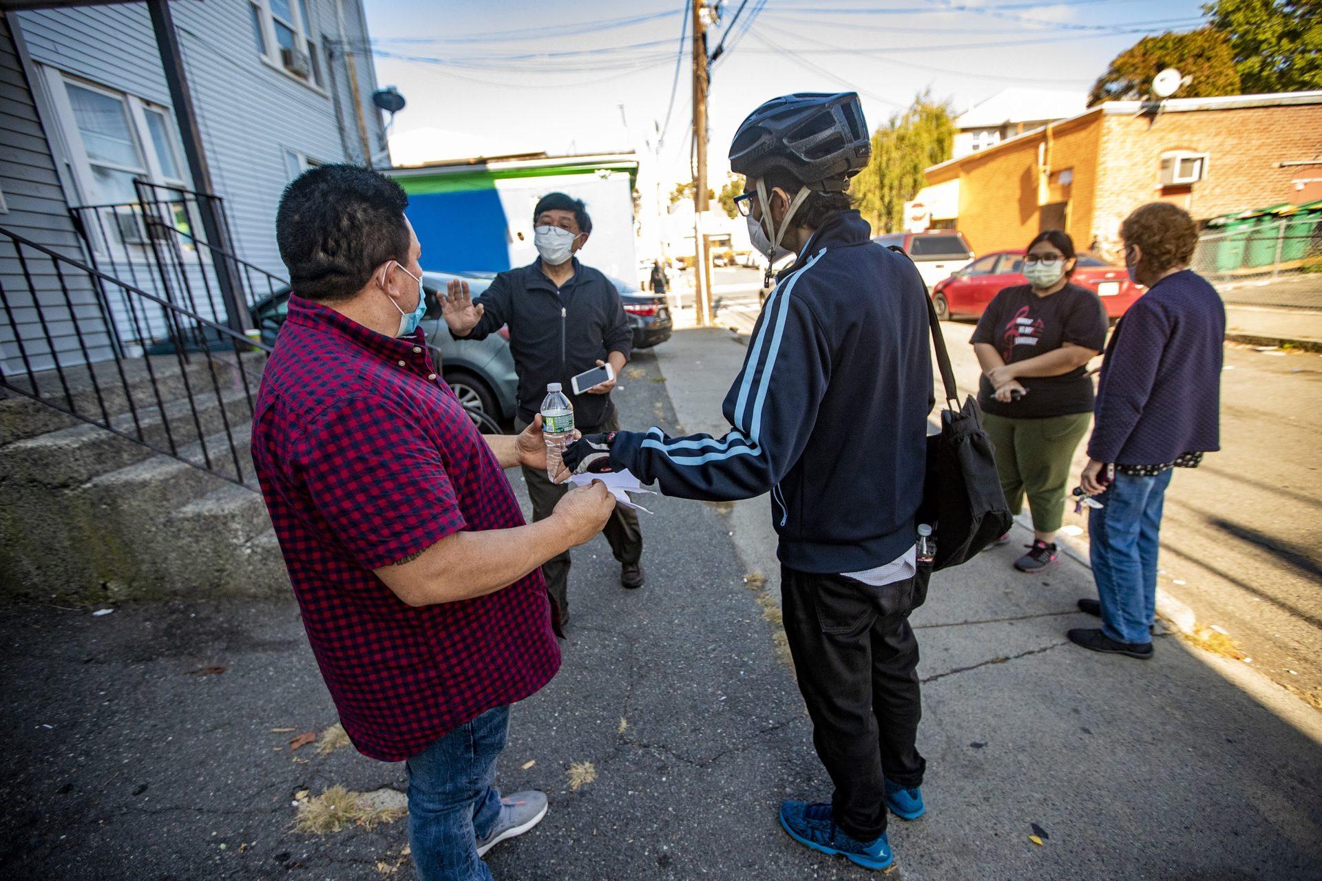 El dueño de la casa, She Ling Wang, camina con su inquilino Robelio Gonzalez (izq) después de que Gonzalez fue detenido por agentes de ICE fuera de su apartamento en Lynn. (Jesse Costa/WBUR)