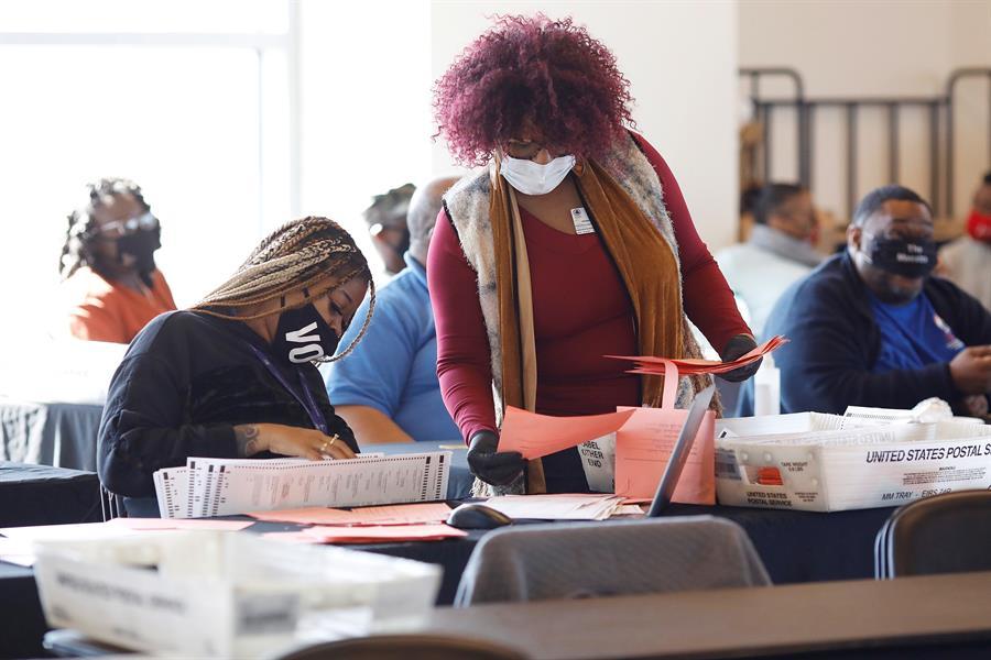 ELECCIONES. funcionarios del condado de Fulton cuentan las papeletas de voto en ausencia en State Farm Arena en Atlanta, Georgia, el 6 de noviembre de 2020. | Foto: Efe.