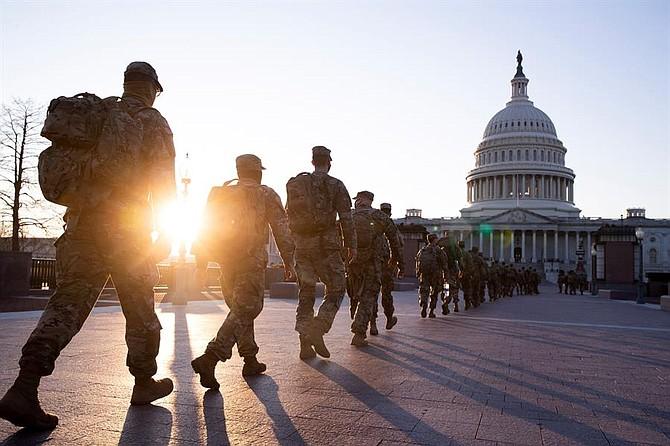 SEGURIDAD. Miembros de la Guardia Nacional de los Estados Unidos se reúnen en los terrenos del frente este del Capitolio, el martes 12 de enero.   Foto: Efe.