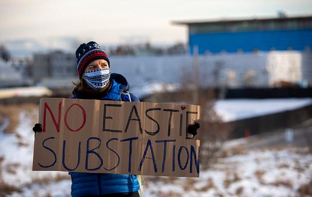 Juliane Manitz de Chelsea en una protesta contra la subestación eléctrica de East Boston. La ubicación propuesta es el área cercada y cubierta de nieve que se encuentra detrás de ella.