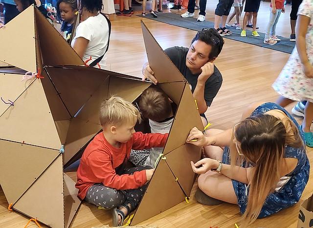 AMBIENTE. Una familia construye la casa imaginaria de un futuro sostenible, con pedazos de cartón.