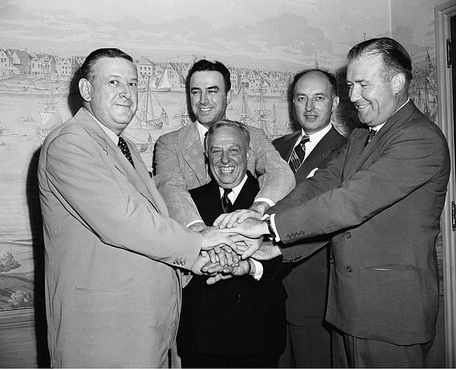 Leo Ferris (segundo de izquierda a derecha) y representantes de la NBL y BAA se dan la mano después de acordar la fusión que crearía la NBA en 1949.